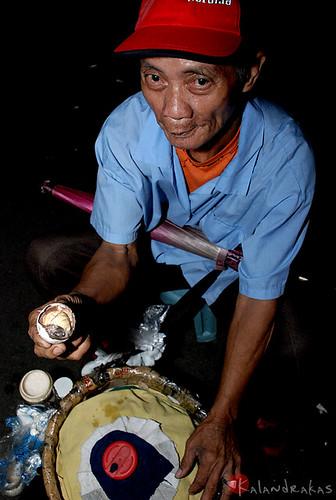 balut egg traditional delicacy vendor oldman man old night ambulant snack squatting snack basket philippines Fuente Osmeña, Cebu City filipino pinoy
