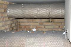 Bild på ventilationsrör i taket på trapphuset i Vammarskolan. På röret ligger flera blyertspennor och papperslappar