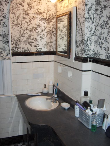 This Victorian bathroom has: black contertops; white sink; mirrored medicine