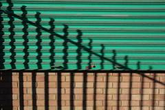 vertical and diagonal on shutters & brick (Phil Dowsing Creative) Tags: lines red green black bricks shadow shadows peterborough market place bike bikes bicycles bicycle railings shutters fabric colour colours color brickwork abstract abstracts pattern patterns natual light sun sunlight