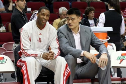 Yao Ming talks with Tracy McGrady before the Rockets try to win their 14th game in a row that would give the team an undefeated record for February.  'Mission accomplished' as Houston soundly beat the Grizzlies 116-95.  Earlier in the day, Yao Ming flew to Charlotte, North Carolina to get a second opinion of his injury from another doctor, then returned the same day to cheer his team to victory.