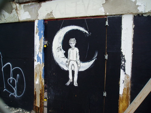 graffiti -- a crescent moon smiling at the young child sitting at its point