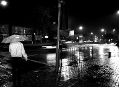 Erdington, at it's sexiest. (MissWickTilleth) Tags: road street uk travel light blackandwhite bw house wet water monochrome rain weather sign night umbrella dark birmingham exposure live reflect commute 1855mm shelter markings moist erdington canon400d tillybrookes sidewalkpavement