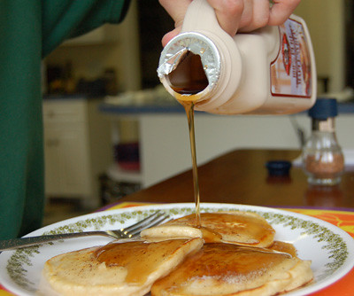 maple syrup poured on pancakes