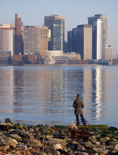 a woman and lower Manhattan reflect on the bank of the Hudson River
