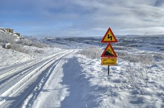 Trouble ahead? (_olasso) Tags: road travel blue winter light sky white mountain snow cold nature sign clouds landscape iceland nikon scenery rocks frost north tracks northern heimrk winterroad d40x