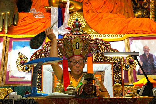 His Holiness Jigdal Dagchen Sakya holding a muhcha (peacock nectar wand) with dutsi (blessed nectar) bestoying empowerment on lamas monks nuns students sitiing in a wish fulfilling jewel throne, Tharlam Monastery Boudha Kathmandu Nepal by Wonderlane