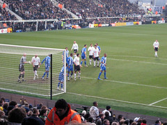 Fulham players in white and Wigan in blue strips
