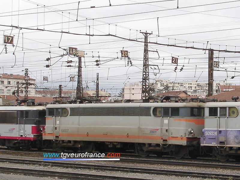 """La locomotive BB 9337 en livrée Béton est garée entre une BB8500 en livrée Multiservice et une BB9300 en livrée """"En voyage""""."""
