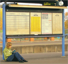 Reading (R A Pyke (SweRon)) Tags: woman clock train reading book sitting sweden platform ground paperback linkping timetable olympuse410