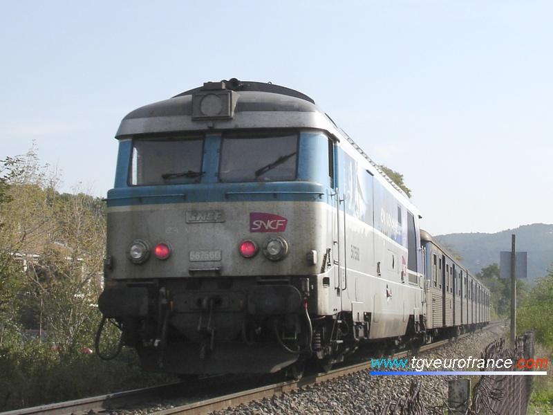 """La locomotive Diesel-électrique BB67560 SNCF en livrée """"En voyage"""" est en pousse d'une rame RIO assurant un TER Aix - Marseille le 27 octobre 2006."""