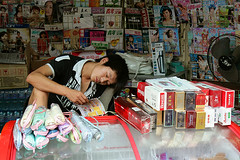 Newsagent's (Pawel Boguslawski) Tags: china man umbrella canon fan newspaper asia read xian agent cigarettes seller 400d lpreading