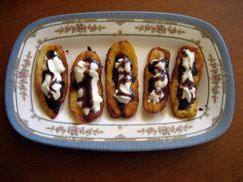 Fried banana slices with whipped cream and chocolate syrup