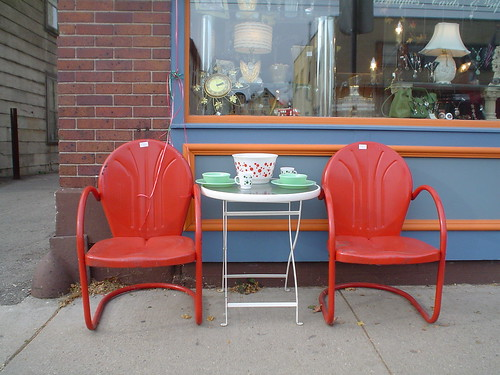 two red chairs in front of antique store