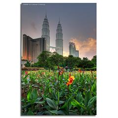 Towers & Flowers (DanielKHC) Tags: park city flowers trees sunset bravo cityscape dusk sony petronas towers malaysia kuala alpha hdr klcc lumpur a100 firstquality photomatix tonemapped 5exp danielcheong flickrplatinum danielkhc