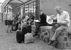 Station2Station (Andy WXx2009) Tags: blackandwhite monochrome streetphotography bags men candid loscristianos people outdoors busstop station travel holiday tourism girl tenerife espana urban spain canaryislands femme women luggage fashion beauty artistic pensioners sitting wall reading brunette street style
