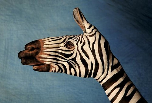 painting of a zebra on the artist's hand