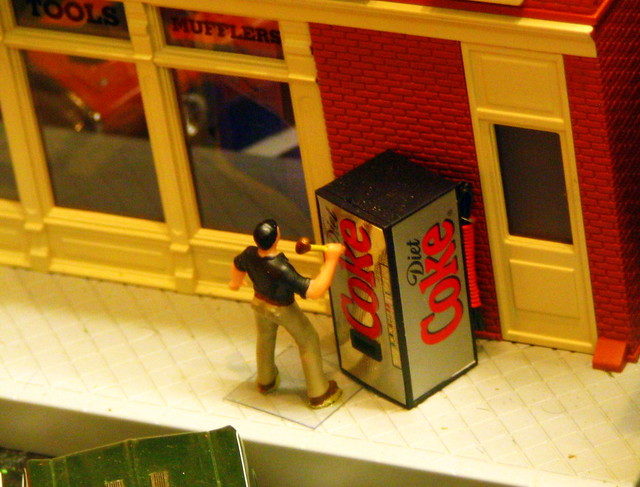 Model Train Display #7: Guy beating a Diet Coke machine with a mallet
