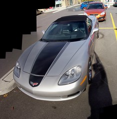 A silver Corvette C6 with a black stripe. (Steve Brandon) Tags: auto shadow autostitch ontario canada chevrolet car geotagged parkinglot automobile gm widescreen ottawa voiture supermarket chevy suburb nepean corvette vette stripmall sportscar c6 chevroletcorvette silvercar photographersshadow generalmotors loblaws picerie stationnement highangle  supermarch chevycorvette americancar    foodbasics  corvettec6 shadowofthephotographer  gmfyi merivaleroad merivalerd ruemerivale cheminmerivale