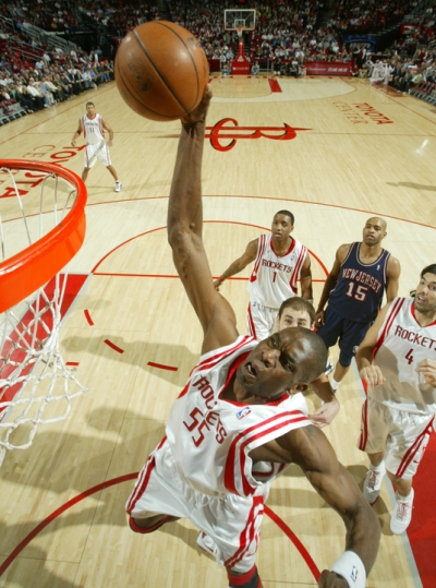 Dikembe Mutombo goes up for a one-handed jam after a Tracy McGrady dish for his only points of the game against the New Jersey Nets.  Mutombo also had 5 blocks to contribute to the Rockets holding the Nets to 30% shooting in a 91-73 victory.