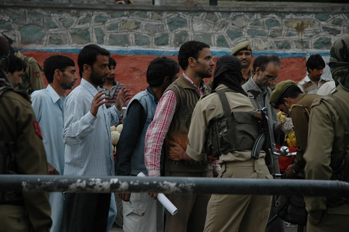 Police frisk civilians in a crackdown in Srinagar