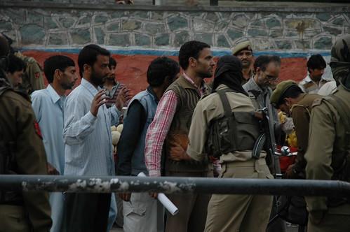 Police frisk civilians in a crackdown in Srinagar