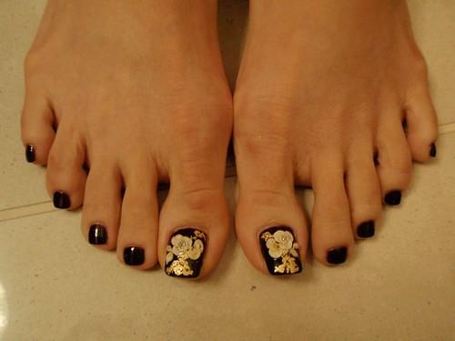 3D nail art design with 3d  flower over black toenails