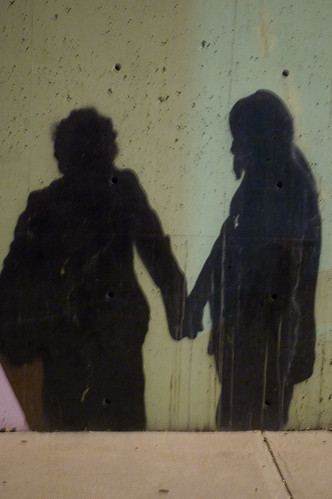 graffiti shadows of two people holding hands