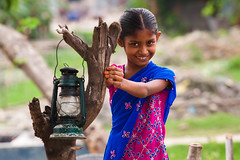 Light of her smile [..Narayanganj, Bangladesh..] (Catch the dream) Tags: life portrait lamp girl smile look rural hurricane rustic shy littlegirl laughter coy bangladesh girlchild narayanganj coysmile gettyimagesbangladeshq2 colorfuldressup