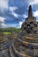 Buddha's Steeple (with a volcano poking through the fog) (Stuck in Customs) Tags: pictures blue sky panorama mountains green texture beautiful look bells indonesia photography nikon shoot photographer shot image photos awesome details d2x perspective images story jungle stunning huge pro portfolio jogjakarta capture sculptures hdr borobudur boro budur stuckincustoms borubudur treyratcliff
