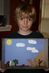 Jacob holding his project (VBJen) Tags: coyote cactus lizard ram diorama roadrunner shrubbery sidewinder desertdiorama