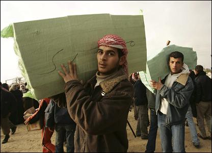 Palestinians carry supplies from Egypt after the wall of separation was blown up in Gaza on Wednesday, Jan. 23, 2008. Gaza has been under total blockade by Israel. by Pan-African News Wire File Photos