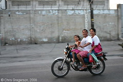 Family Speeding by on a Motorcycle, Angeles City (Chris Gregerson) Tags: road family man male horizontal youth speed asian person parents dangerous asia child risk philippines transport young fast cycle transportation commute motorcycle vehicle filipino trike youthful youngster pilipinas luzon helmets pampanga risky headinjury clarkairbase angelescity underdeveloped preschoo republicofthephilippines angelescityandclarkairbase clarkspecialeconomiczone chrisgregerson