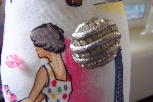 Closeup of yummy vintage button on doll