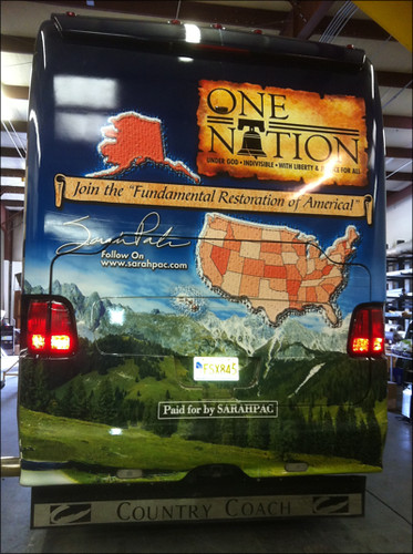 the backside of Sarah Palin's bus. It is humongous. It reads gaudily, One Nation: Join the 'Fundamental Restoration of America!' There is a picture of Sarah Palin's signature, a large map of the United States, Alaska being particularly prominent, and in smaller lettering at the bottom 'Paid for by SarahPac'