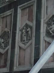Hexagonales Relief am Glockenturm, das zwei Diskutanten zeigt