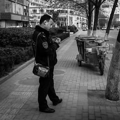 A busy officer (Go-tea 郭天) Tags: street urban city outside outdoor people bw bnw black white blackwhite blackandwhite monochrome asia asian china chinese shandong canon eos 100d 24mm prime qingdao huangdao police officer man bag stand standing cut cutting nails hands fingers concentration concentrated motobike motorbike winter cold jacket uniform duty off policeman work portrait trees road buildings busy