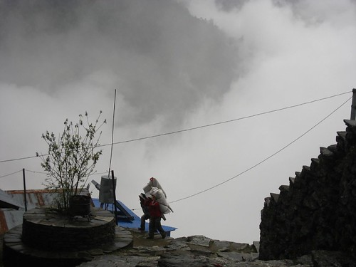 Porters carry their loads up through the clouds
