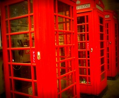 Three red telephone boxes, standing in a row