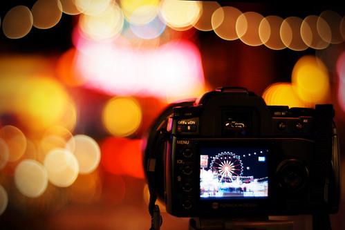 Fotografía de una cámara vista desde detrás enfocando a una noria de noche, el fondo queda desenfocado