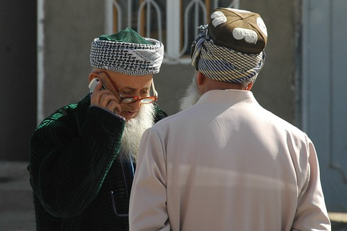 Imam in Dushanbe, Tajikistan on a mobile phone