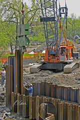 ICE 812 Vibro-Hammer vibratory pile driver/extractor drives sheet piles to form cofferdam at Huron River. By Flickr User RiCarr.