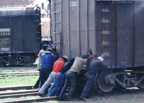 A group of men pushing a railway freight car