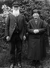 Mr and Mrs Andersson, Skederid, Uppland, Sweden (Swedish National Heritage Board) Tags: portrait woman man smile hat standing beard outdoors glasses couple coat fulllength husband cap older wife eyeglasses riksantikvariembetet theswedishnationalheritageboard