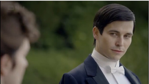Thomas from Downton Abbey, a white man with dark hair, wears a tuxedo and a smug look on his face