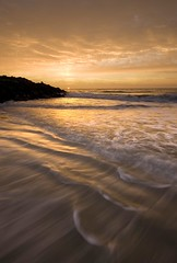 East Beach Sunrise (blakelipthratt) Tags: ocean longexposure two sky sun beach water st rock sunrise canon ga georgia island sand horizon sigma wave brunswick atlantic 1020mm simons eastbeach goldenlight digitalblend xti 400d 2exposure