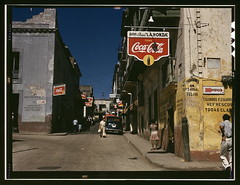 Street in San Juan, Puerto Rico  (LOC) (The Library of Congress) Tags: street city light urban signs colour film luz latinamerica car fashion sign architecture corner buildings geotagged calle vintagecar san shadows dress gente juan oldsanjuan puertorico capital transport coke ciudad streetscene powerlines sanjuan spanish trfico esquina signage pedestrians caribbean libraryofcongress cocacola streetcorner letrero viejo latinos 1941 viejosanjuan boricua sunnyday commercialism softdrink trafico tome vintagesign analogic colonialism attire peatones lahonda foottraffic borinquen puertorriqueos clsica reposteria newtopographics escenacallejera xmlns:dc=httppurlorgdcelements11 dc:identifier=httphdllocgovlocpnpfsac1a34067 geo:lat=18465912 geo:lon=66117193 laisladelencanto vintagecokesign milnovecientocuarentauno