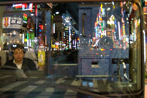 Shinjuku reflected in a bus window, Tokyo, Japan.