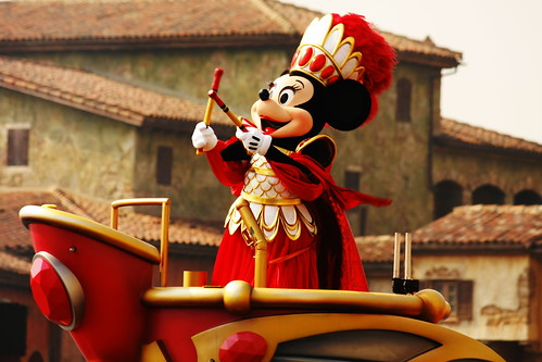 Minnie, the Spirit of Love, is on top of her Griffon in a strong red outfit with the drum sticks.