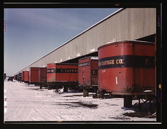 Truck trailers line up at a freight house to l...